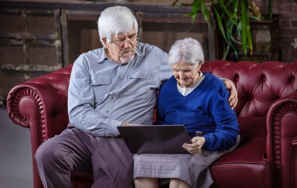mature-man-and-senior-woman-using-laptop-while-sit-TNHGQV2