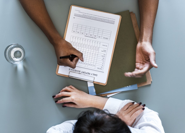 aerial-view-of-doctor-writing-patient-daily-report-PAMN3UA