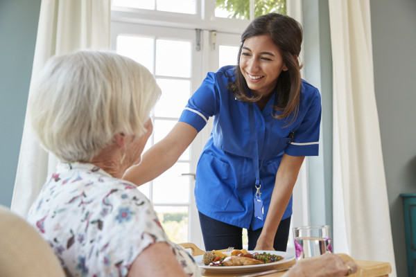 care-nurse-serving-dinner-to-a-senior-woman-at-hom-PQHJS4A